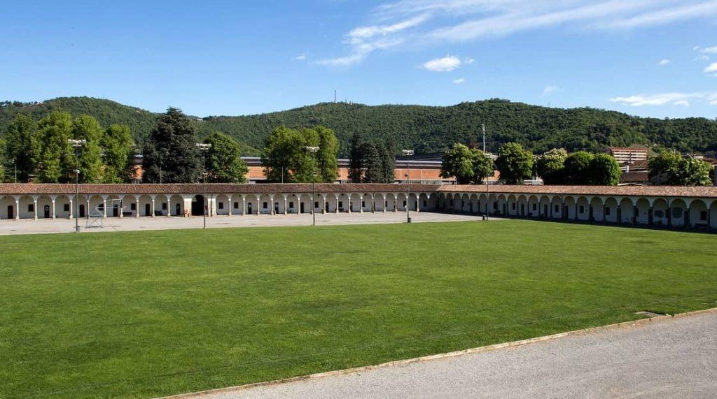 Panoramica del Lazzaretto di Bergamo. Nella fotografia si vedono il porticato interno dietro al quale ci sono le porte e le piccole finestre delle celle. Al centro del chiostro un ampio prato verde.